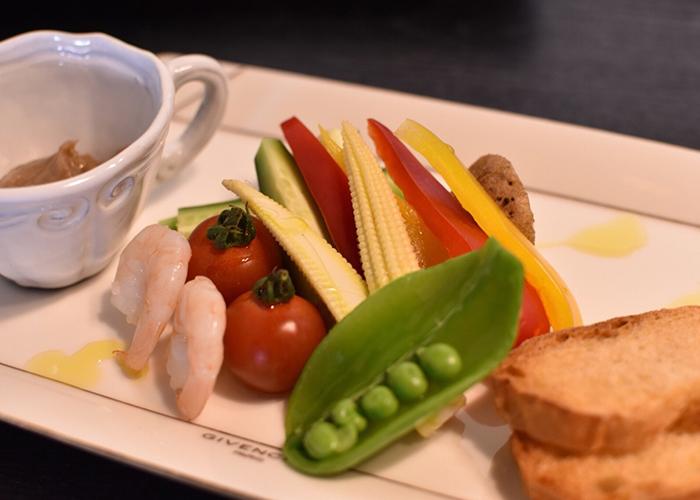 色とりどりの野菜や小エビやバゲットと小さなコップに入ったソース